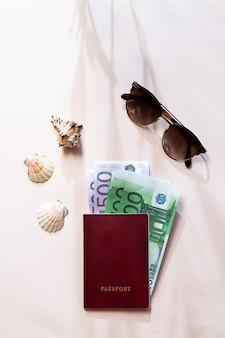 Um passaporte com dinheiro, óculos escuros e conchas do mar, deitado sobre a mesa rosa claro