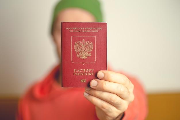 Um passaporte internacional estrangeiro russo nas mãos de um jovem cidadão russo.