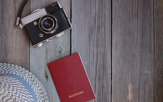 Um passaporte, uma câmera vintage, um chapéu em fundo de madeira