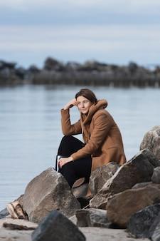 Um passeio romântico de uma mulher de cabelo encaracolado com um casaco de lã bege posando em uma pedra no mar