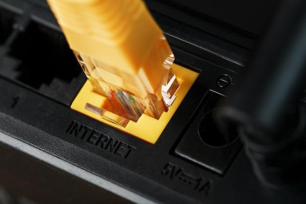 Um patch cord amarelo é inserido na porta wi-fi do roteador para acessar a internet