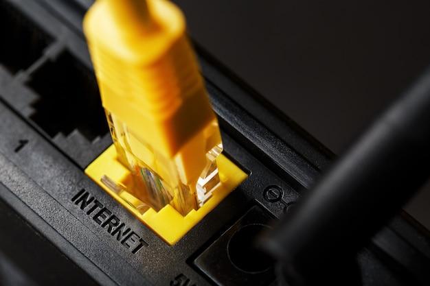 Um patch cord amarelo é inserido na porta wifi do roteador para acessar a internet