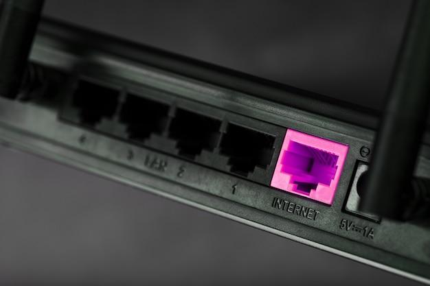 Um patch cord rosa é inserido na porta wi-fi do roteador para acessar a internet