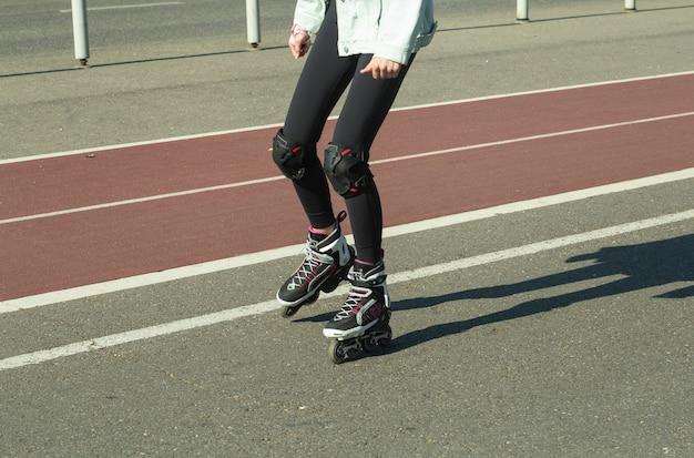 Um patins de menina em uma ciclovia na cidade no verão. férias de verão na cidade e um estilo de vida ativo.