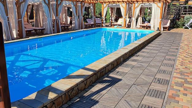 Um pátio com piscina, espreguiçadeiras