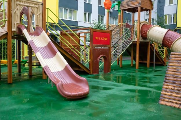 Um pátio de prédios altos com um playground moderno e grande feito de madeira e plástico em um dia chuvoso de verão sem pessoas. parque infantil vazio ao ar livre. um espaço para jogos e esportes infantis.