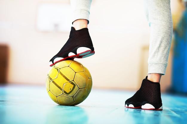 Um pé humano descansa na bola de futebol no chão de concreto. foto de uma bola de futebol e tênis em um piso de madeira.