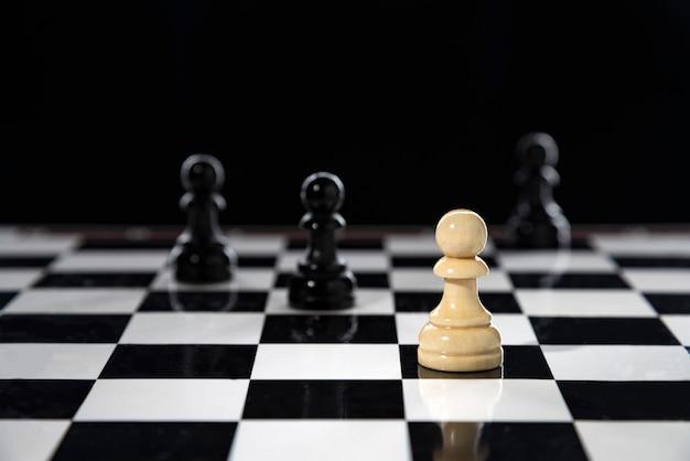 Um peão branco fica em um tabuleiro de xadrez contra preto