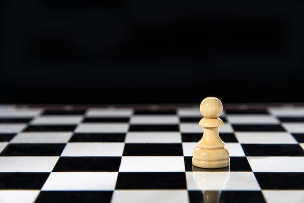 Um peão branco solitário fica em um tabuleiro de xadrez.