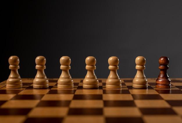 Um peão preto contra muitos outros. diferente contra o conceito de monopólio e desigualdade