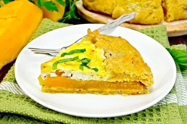 Um pedaço da torta de abóbora, queijo feta salgado, ovos, creme e ervas em um prato na toalha, manjericão em uma placa de madeira escura