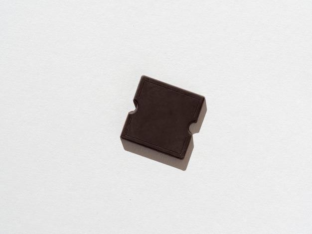 Um pedaço de barra de chocolate escuro em um fundo de papel branco. uma sombra dura. produto doce e de alto teor calórico. vista superior, configuração plana