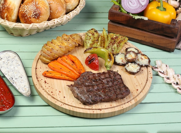 Um pedaço de bife com legumes grelhados na placa de madeira.