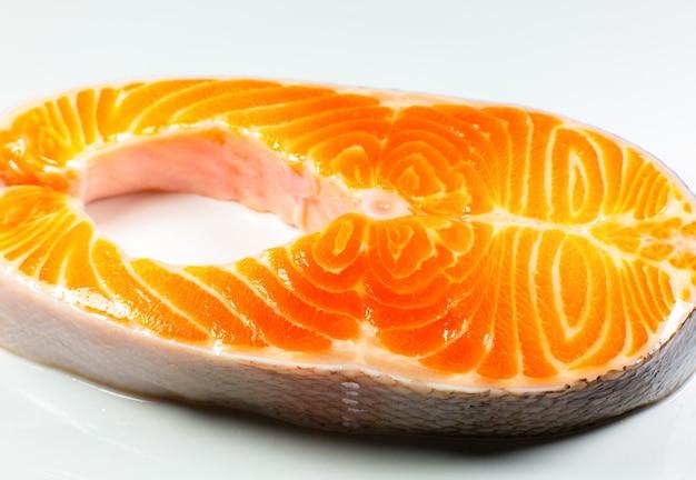 Um pedaço de bife de salmão fresco no fundo branco. vitamina ômega 3, estilo de vida saudável. comida vegetariana natural. vista do topo. feche a foto.