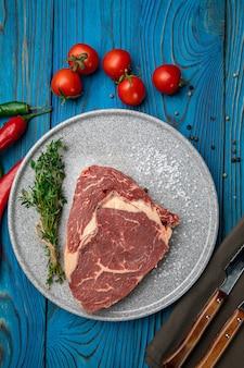 Um pedaço de bife de vitela cru em um prato redondo com temperos