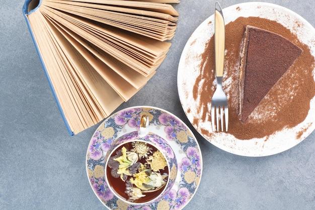 Um pedaço de bolo com chá aroma e livro