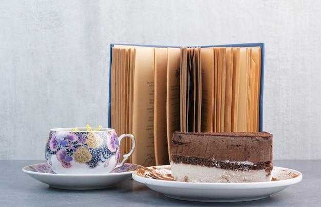 Um pedaço de bolo com chá de aroma e livro.
