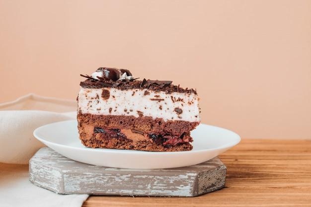 Um pedaço de bolo com chocolate e cerejas, bolo em um prato em uma parede bege