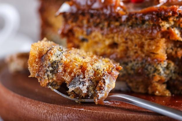 Um pedaço de bolo com creme de caramelo cortado com colher em uma placa de cozinha de madeira marrom fundo de madeira