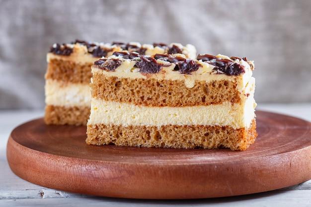 Um pedaço de bolo com creme do leite e da manteiga em uma placa de madeira da cozinha, fundo branco.