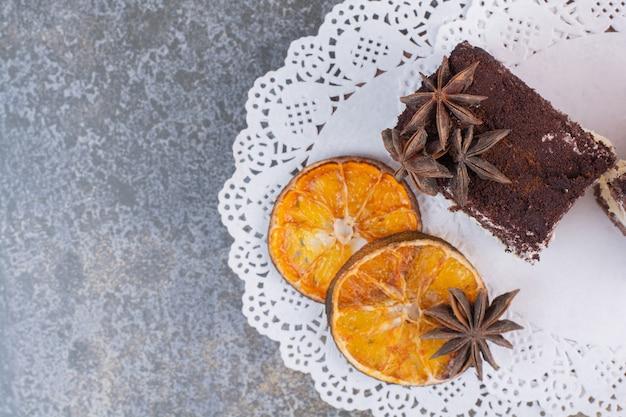 Um pedaço de bolo com laranja seca e anis estrelados na superfície branca