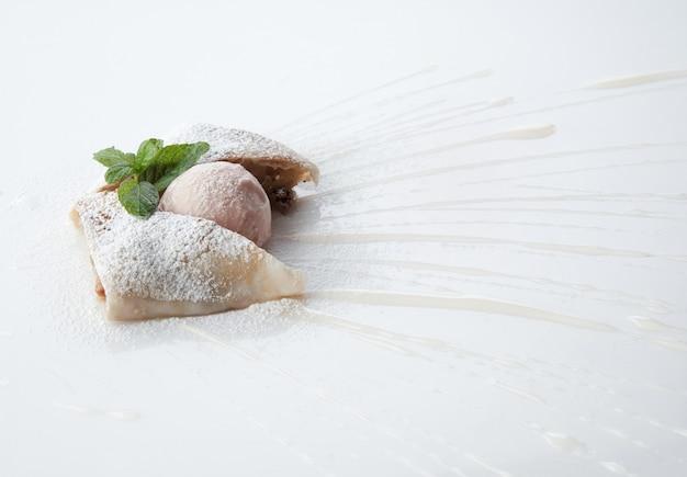 Um pedaço de bolo com molho doce sobre fundo branco