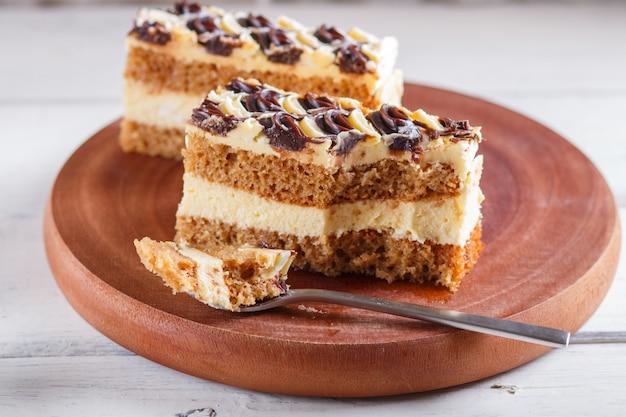 Um pedaço de bolo com o creme do leite e da manteiga cutted com colher em uma placa de madeira da cozinha, tabela branca.
