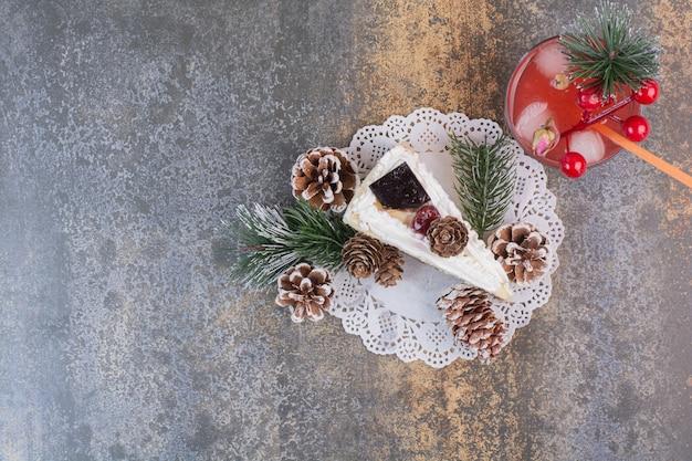 Um pedaço de bolo com pinhas e suco de morango gelado com canudo