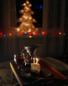 Um pedaço de bolo com velas acesas em um quarto escuro. aniversário ou feriado - uma surpresa