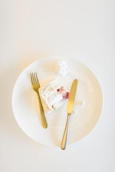 Um pedaço de bolo de casamento em um prato branco com vista superior de gancho e faca em um espaço de cópia de fundo branco mesa para texto
