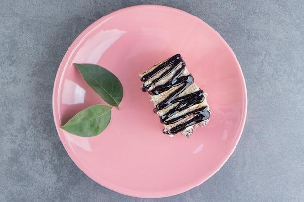 Um pedaço de bolo de chocolate com folhas em um prato rosa