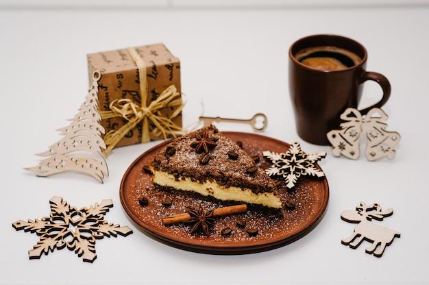 Um pedaço de bolo de chocolate delicioso com creme, grãos de café em um prato marrom, xícara de café é isolado em uma superfície branca. canela, anis. decorações e presentes de natal. vista lateral.