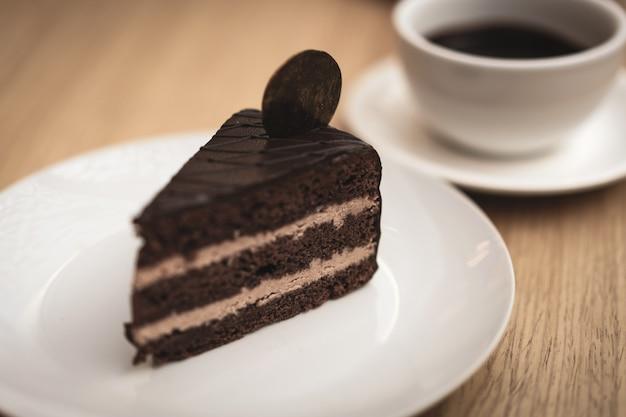 Um pedaço de bolo de chocolate delicioso em um prato branco e uma xícara de chocolate quente
