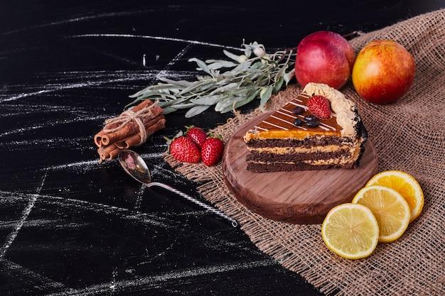 Um pedaço de bolo de chocolate em prato redondo de madeira com canela e várias frutas.