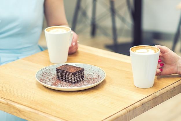 Um pedaço de bolo de chocolate saboroso em cima da mesa no fundo das mãos com xícaras de café.