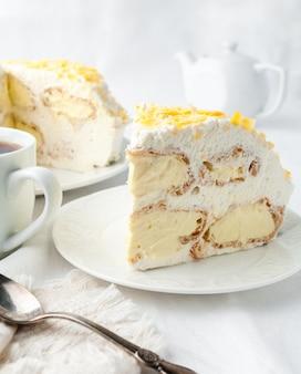 Um pedaço de bolo de creme com chantilly decorado com gotas de chocolate amarelas feito em casa em um prato branco perto de uma colher e uma caneca no fundo está um prato com bolo e um bule de chá branco