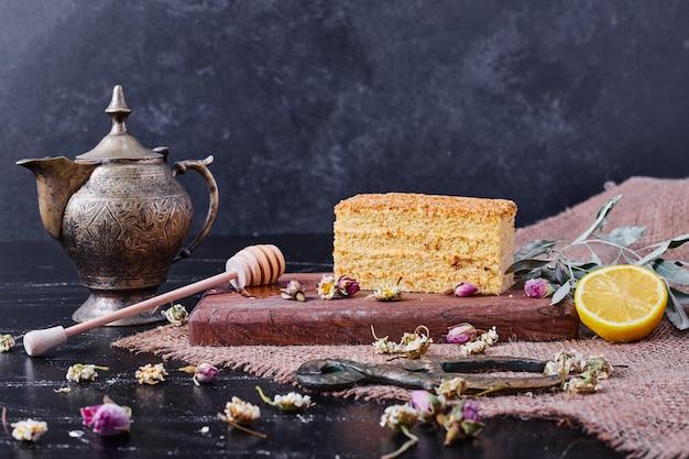Um pedaço de bolo de mel com flores secas e uma xícara de chá clássica na mesa de mármore.