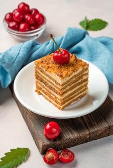 Um pedaço de bolo de mel decorado com cerejas frescas em um fundo claro. vista lateral, vertical.