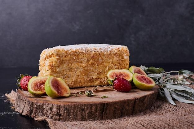 Um pedaço de bolo de napoelão em fundo escuro com figos e morangos.
