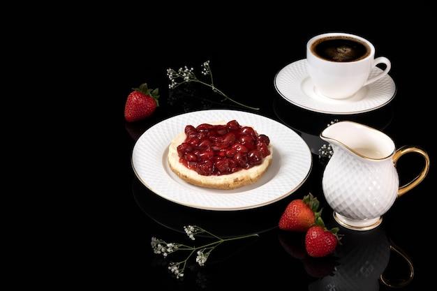 Um pedaço de bolo de queijo delicioso cerejas na chapa branca com café preto.