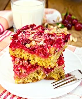 Um pedaço de bolo doce com cerejas em um prato, guardanapo, garfo, leite em um copo sobre um fundo de tábuas de madeira