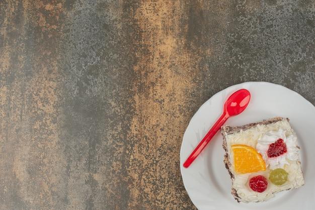 Um pedaço de bolo doce com colher vermelha em prato branco