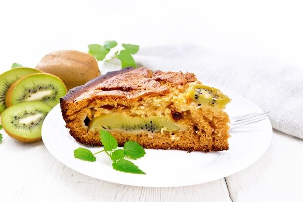 Um pedaço de bolo doce com kiwi e mel, hortelã e garfo em um prato, toalha em um fundo de placa de madeira