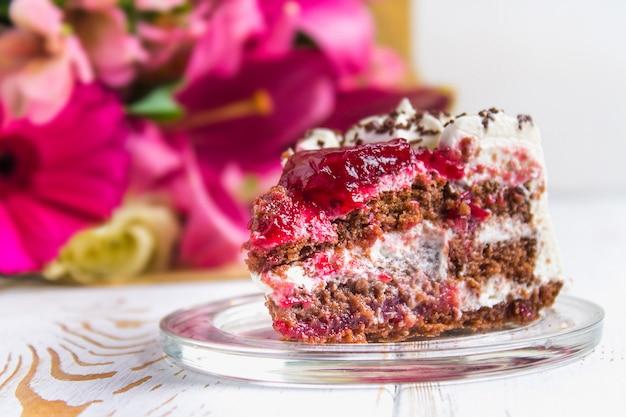 Um pedaço de bolo e um buquê de flores sobre uma mesa de madeira branca.
