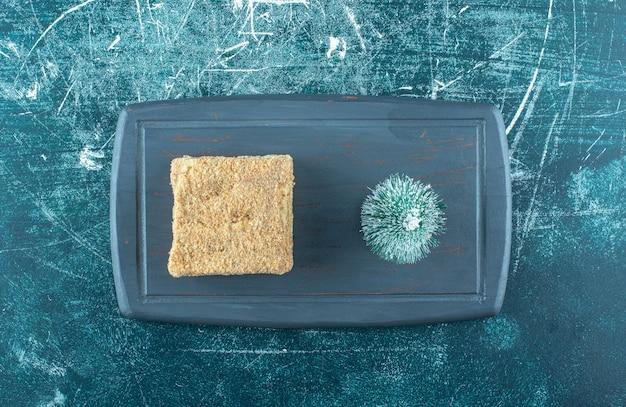 Um pedaço de bolo saboroso com uma pequena árvore de natal em um prato escuro. foto de alta qualidade