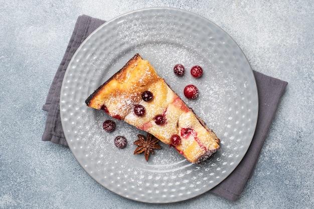 Um pedaço de caçarola de torta de queijo cottage com amora bagas e especiarias canela e anis em um prato.