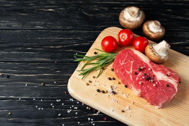 Um pedaço de carne crua suculenta com alecrim em uma placa de corte em uma mesa de madeira preta. Foto Premium