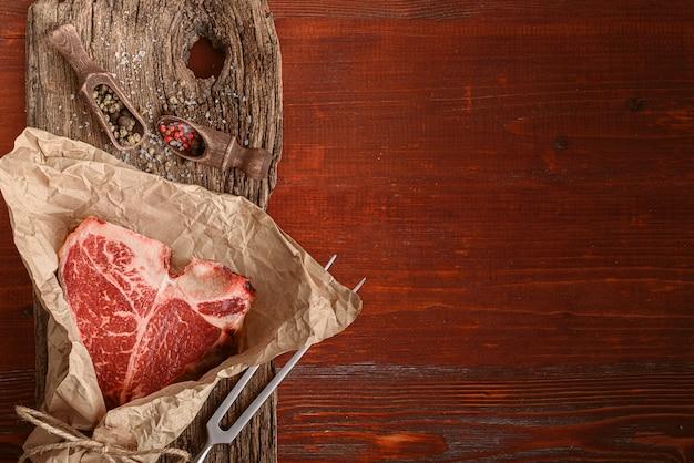 Um pedaço de carne fresca da fazenda t-bon sem ogm embrulhado em papel de embrulho ecológico