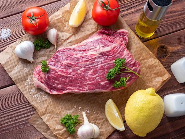 Um pedaço de carne marmorizada repousa sobre um pergaminho cercado por ervas, alho, tomate, limão e muito mais
