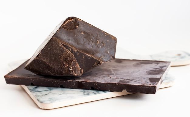 Um pedaço de chocolate lascado com uma barra de chocolate amargo em uma placa de mármore clara.